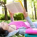 Immagine di una ragazza che legge in un prato