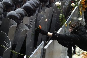 KIEV, UKRAINE: A supporter of pro-Western opposition leader Viktor Yushchenko places a flower on a riot policeman's shield as they guard the Presidential office building in Kiev, 24 November 2004. The political crisis in Ukraine deepened Wednesday as opposition leaders refused to negotiate over a disputed presidential election and their supporters entered a third day of mass street protests. AFP PHOTO / VIKTOR DRACHEV (Photo credit should read VIKTOR DRACHEV/AFP/Getty Images)