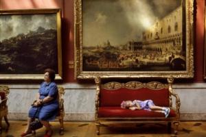 """Leningrado 1987 Nei saloni dell Ermitage, una bambina riposa tranquilla sotto il quadro di Canaletto """"L'arrivo dell'ambasciatore francese a Venezia""""."""